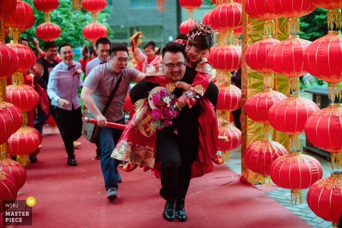 Shanxi Wedding Photojournalist | the groom carries the bride on his back as he is followed by the bridal party
