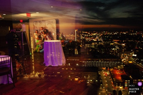 Boston Wedding Photojournalist | guests at the photo booth are reflected in this night time city reception