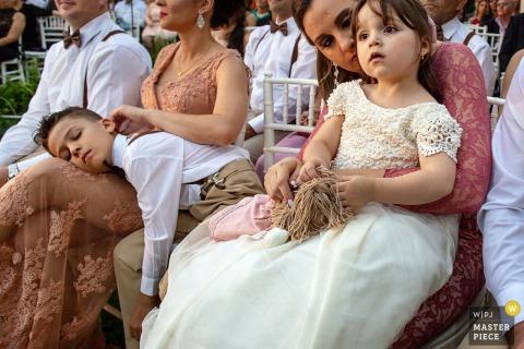 Das Blumenmädchen und der Ringträger von Goiânia warten geduldig durch eine lange Hochzeitszeremonie im Freien