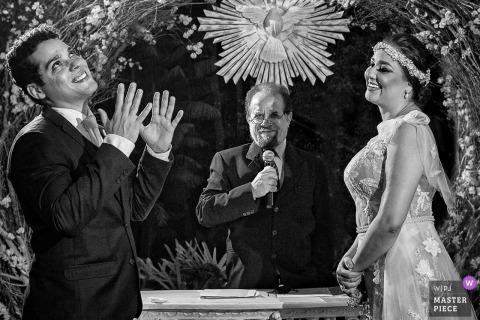 Goiânia Hochzeitsfotojournalist | die braut und der bräutigam mit dem amtierenden in einem schwarz-weißen zeremonie bild