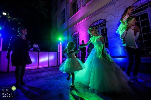 Saint Tropez, France mariée dansant avec petite fille à la réception avec des lumières colorées DJ
