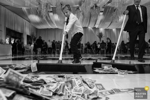 Dollar bills are pushed into a pile with brooms on the dance floor at this South Lake Tahoe, Nevada reception party