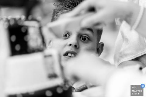 Legau, Deutschland Hochzeitsfotojournalist | Ein Junge mit eifrigen Augen sieht zu, wie die Hochzeitstorte von Braut und Bräutigam geschnitten wird