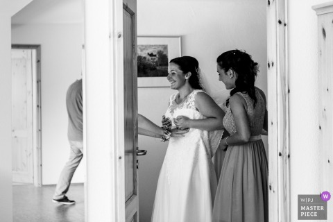 Nettetal, Germany Wedding Photojournalist | the bride does final checks as she puts on her dress in preparation of the wedding ceremony