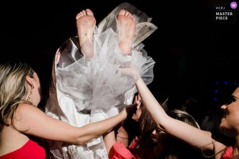 Macaé Wedding Photojournalist | the brightest tossed overhead on the dance floor by the bridesmaids in red dresses