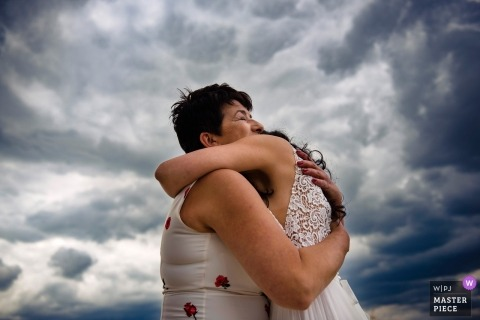 Budapest Wedding Photojournalist | bride and mom hugging outside under the dark clouds