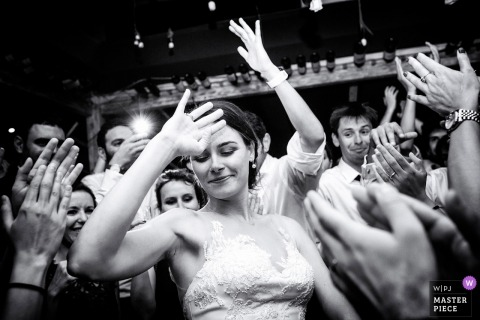 Budapest Wedding Photojournalist | the bride dances in a black-and-white image - swimming in a sea of clapping hands