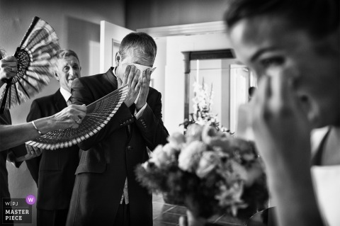 Valencia Wedding Photojournalist | black-and-white photo of family fanning the bride and groom as they cry
