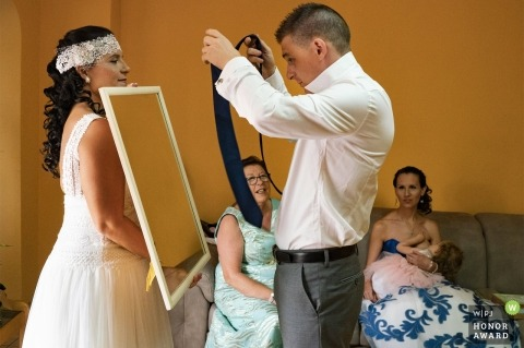 Valencia bridesmaid helps groom with getting his tie on