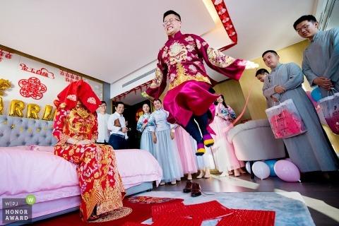 Der Bräutigam leidet unter schmerzhaften chinesischen Türspielen, um sein braut springendes Seil auf spitzen Pads zu gewinnen