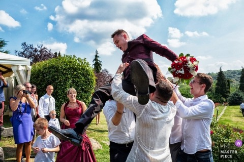 Turin Wedding Photojournalist | the groom is lifted above the men as he holds a bouquet of flowers at the Tenuta castello Cerrione