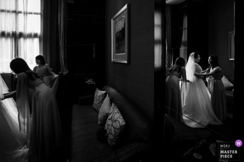 Fuzhou Wedding Photojournalist | the bride receives help with her gown in this black-and-white image