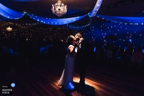 New South Wales Wedding Photojournalist | the bride and groom kiss during the first dance under a reception spotlight