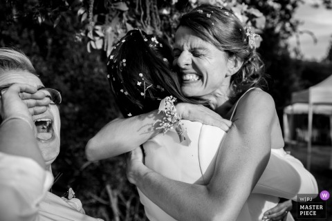 Paris Wedding Photojournalist | the bride celebrates with the excitement and a hug at the outdoor wedding