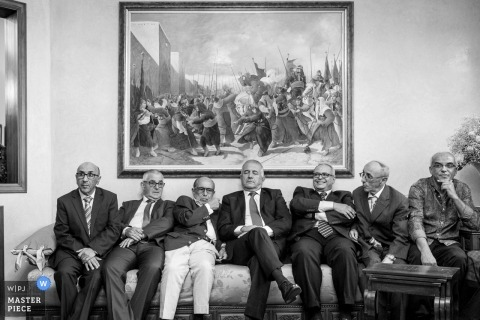 Paris Wedding Photojournalist | a group of elderly men are seated on the big couch under a painting at the reception