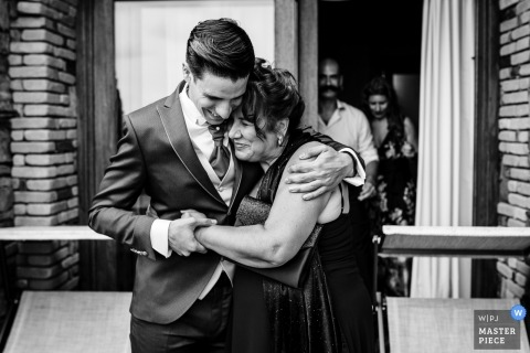 Cagliari Wedding Photojournalist | Black and white image of groom hugging his mother outside