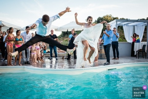 Sardinia Wedding Photo of the bride and groom jumping into a pool at the reception party