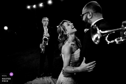 Siena Wedding Photojournalist | the dancing bride and groom our frames by a saxophone and trumpet in this black and white reception photo