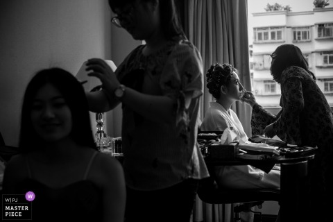 Fuzhou Wedding Photojournalist | the bride has her makeup applied next to the hotel window