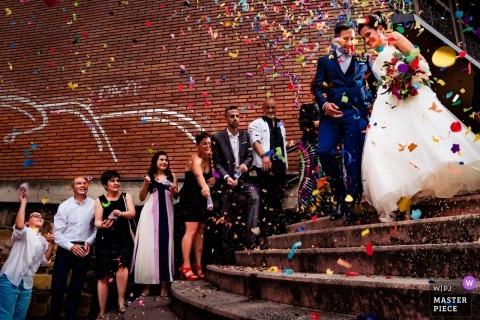Spain Wedding Photojournalist | the bride and groom come down the stairs as guests throw Rainbow colored confetti