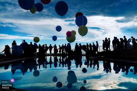 Croatia Wedding Photojournalist | silhouette reflections and balloons filled this blue tone wedding reception image