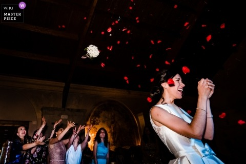 Spain Wedding Photojournalist | Color image of the bride tossing her bouquet with red flower petals filling the air
