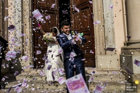 italian wedding Photojournalist - bride and groom exit the church to a barrage of confett and flowers