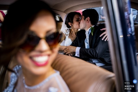 Reggio Calabria Wedding Photo of the bride and groom kissing in the backseat of their vintage wedding car