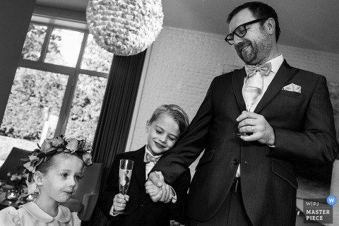 Roeselare Wedding Photojournalist | the groom the hand of the ring bearer with a flower girl close by