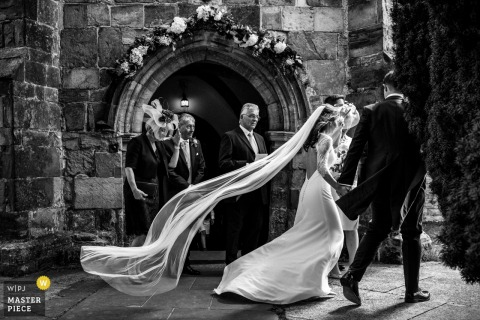 bride's veil catches the wind outside of the church in Ticehurst, UK