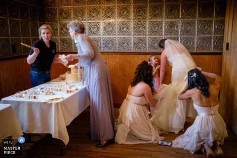 Stevensville, Montana Wedding Photojournalist | the bride gets her dress bustle as vendors cut up the cake
