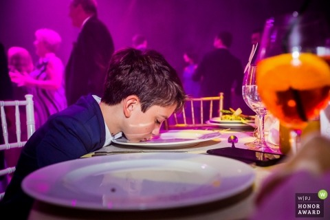 Young boy cleaning his cake plate at this Romania wedding reception