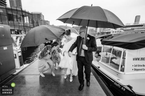 Australien-Brautparty, die vom Boot im Regen mit Regenschirmen bei den Melbourne Docklands erhält.