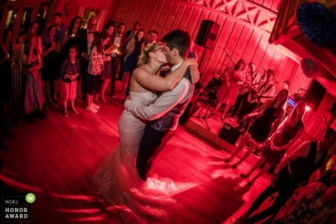 Bride and groom kiss during their dance in Germany - Straubing wedding reception with red lights