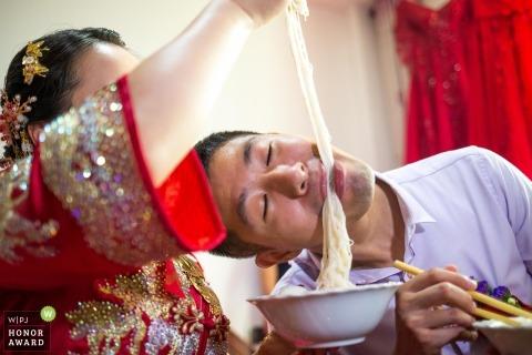 Braut und Bräutigam, die Nudeln vor Hochzeitszeremonie in China genießen.