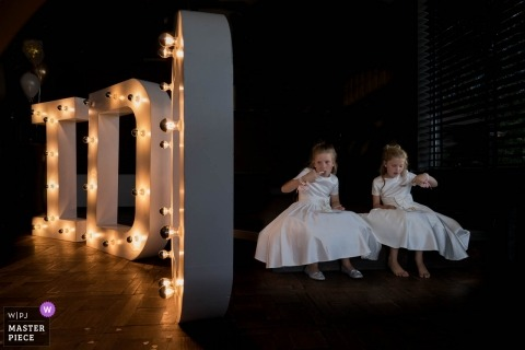 Netherland Wedding Photojournalist | Image of two young flower girls next to a very large I do electric sign