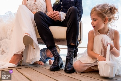 Netherlands Wedding Photojournalist | a young girl and boy are close to the bride and groom as they're seated in a chair