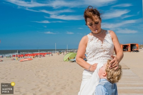 Netherland bride uses her wedding gown to wipe the nose of a small boy