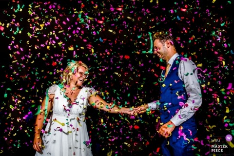 Antwerpen Wedding Photojournalist | colorful confetti Falls over the bride and groom as they dance