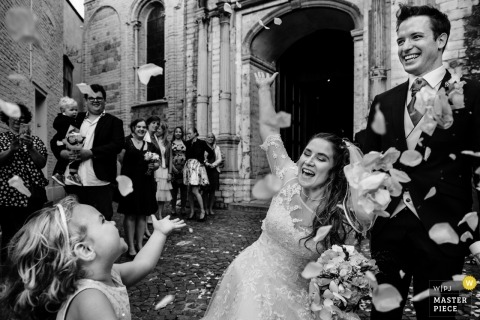 The bride and Graham celebrate as a flower girl and guests throw flower petals over their heads