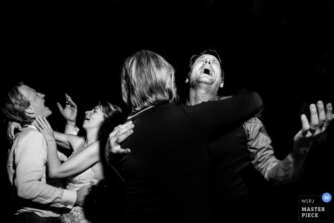 Antwerpen Wedding Photojournalist | Black and white image of guests dancing and singing at this night time reception