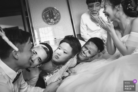Hunan Wedding Photojournalist | the groomsmen wear paper masks as they look at the groom while the bride laughs
