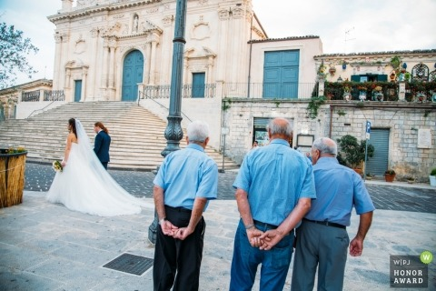 Sicily men watch the bride and groom walking passed the Palazzolo Church they were married in