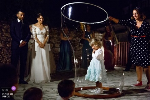 during wedding reception in cosenza a little girls is inside a bubble soap | cosenza photographer