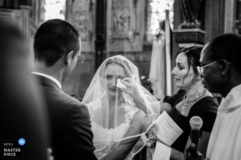 Haute-Garonne Wedding Photojournalist | the maid of honor wipes a tear under the brides veil during this ceremony