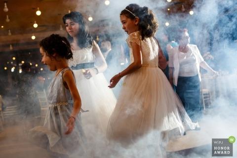 Niños de Bucarest disfrutando de la recepción y las máquinas de niebla de DJ en la pista de baile.