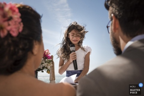 Buzios, Rio de Janeiro, Brazil Wedding Photojournalist | a young girl cries while holding a microphone as she speaks to the bride and groom during this outdoor wedding ceremony