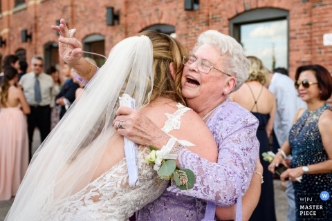 Grandmother hugging bride with enthusiasm in Montreal, Quebec