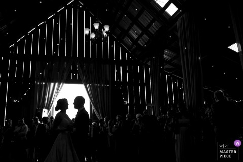 Mendocino, California Wedding Photojournalist | the bride and groom are framed in the barn door in this silhouette Image during their first dance at the reception
