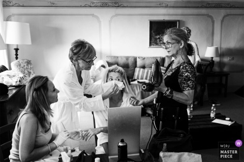 Lucca - Italy Wedding Photojournalist | the bridal team helps the bride prepare for the wedding in this black-and-white photo